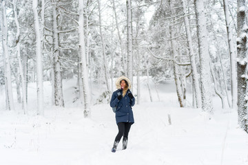 Beautiful woman standing among snowy trees in winter forest and enjoying the joys of Winter