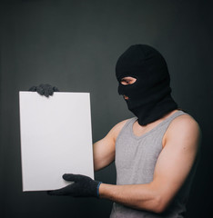 A man in a black mask holds a white sheet. A guy in a balaclava and wearing gloves holds a white empty square. A man on a gray background holds a canvas.