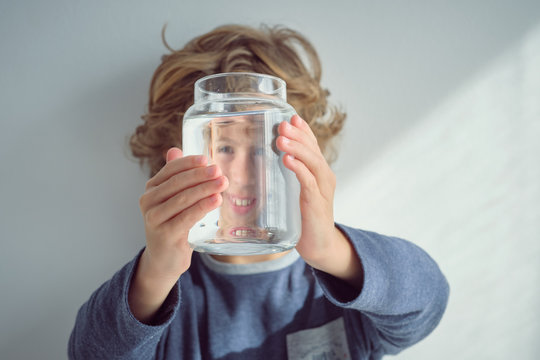 Cute little boy smiling and holding glass jar with clean water in front of face while standing near white wall