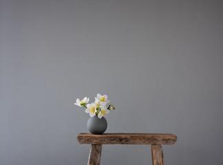 Runde, graue Vase mit Frühlingsblumen auf altem Holzhocker