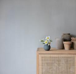 Blumenvase mit Frühlingsblumen auf Schrank mit natürlicher Dekoration