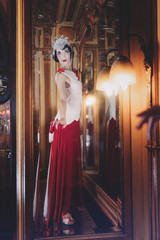 Woman wears an art deco evening gown and looks in the mirror
