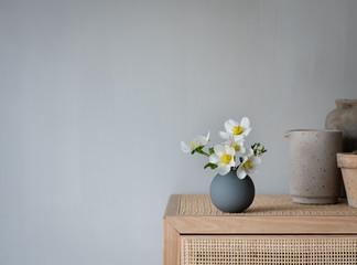 weiße Blume  in grauer Vase auf einem Schrank im skandinavischen Design