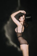 Woman poses in tophat and lingerie