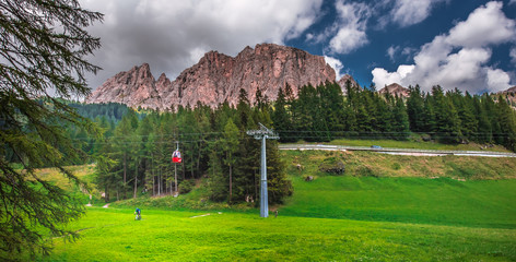 Fototapeta rowery górskie, góry rowerzysta, rowerzyści, koła, góry, Doklomity, ścieżka, kierownica, sport, sportowiec, bike, zieleń klimat, Italia Włochy, wyciąg, kolejka, gondola, iglaki, choinki, las, słup obraz