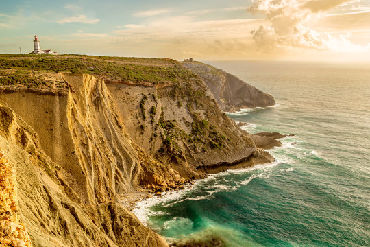 The Espichel Cape. Amazing view of lighthouse and seascape during golden hour. Atlantic Ocean during sunset