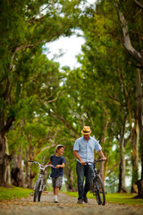 Father and son walking and pushing their bicycles.
