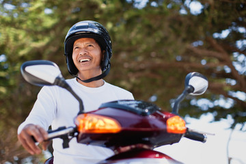 Man happily sitting on scooter with helmet on.