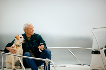 Man relaxing with his dog on the deck of a boat.