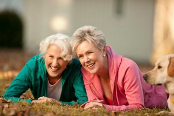 Two laughing senior women lying next to each other in a park