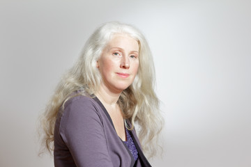 Headshot of a mature woman with beautiful curly long gray hair in front of white background, copy space.