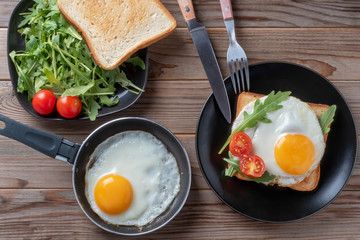 Top view of fried eggs on black plate and pan with fork, rukkola and mushrooms