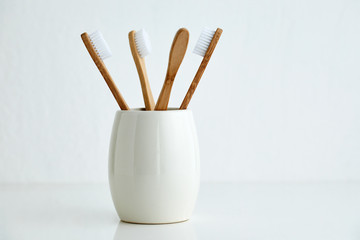 Four bamboo toothbrushes in a glass on a gray background