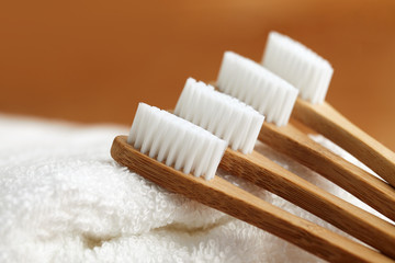 Four bamboo toothbrushes on white towel, close up