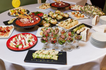dishes on the table, salads in glasses, snacks, reception