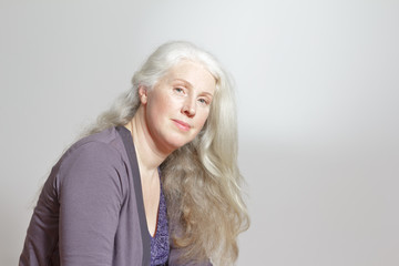 Portrait of an attractive mature woman with beautiful long gray hair in front of white background, copy space