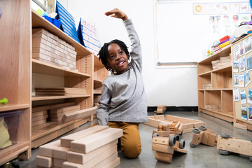 Boy playing with wooden blocks and trucks