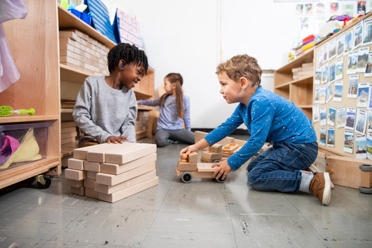 Students playing with wooden toys in classroom