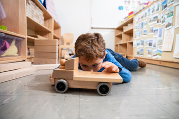 Boy playing with wooden truck in classroom