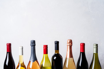 Tops from different kinds new bottles of champagne, white, red wine on light background