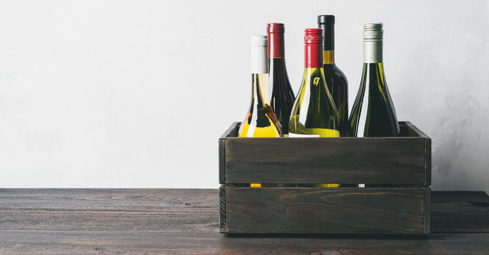 Set of different kinds bottles of champagne, white, red wine in wooden box on light background