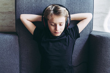 Top view of blonde boy listening to music with headphones closed eyes, spending free time relaxing singing student lying on its back comfortably relaxed at home. Domestic scene Playing with smartphone