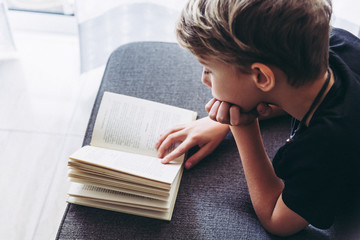 Blond boy barefoot reads book with his face leaning on a hand, student lying down reading the lesson comfortably relaxed, diligent child reads a story, young man plunges into culture Top view Close up