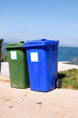 Trash can, garbage bin, recycling bin in tourist complex by sea, side of road waiting to be picked up by garbage truck. Blue and green containers for waste sorting, sort garbage for paper and glass.