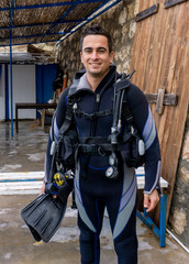 Portrait of a young handsome man diver ready to go scuba diving with cold water wet suit, fins, buoyancy compensator, regulator, alternate air source, weight belt, pressure gauge, oxigen tank