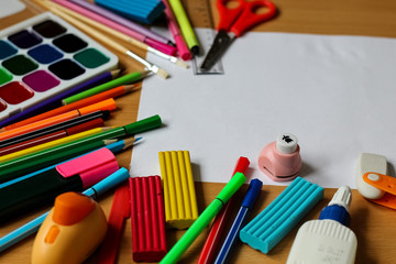 Top view on table with blank sheet of paper. Back to school concept with space for text. Color paints with paint brushes, pencils and plasticine. Kids painting concept. Children art.