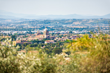Many olive trees leaves framing town or village city of Bastia Umbra by Assisi with church in Umbria, Italy bokeh foreground during sunny summer day nobody