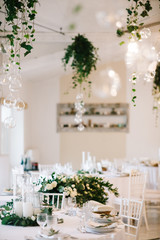 Wedding dinner table set. Classy white decor with greenery
