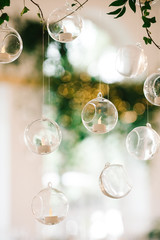 Little balls with candles hang from floral garland over wedding dinner table