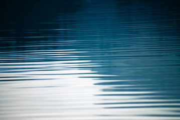 Amazing textured background of calm blue clean water surface. Sunshine in mountain lake close-up. Beautiful ripples on shiny water in sunny day. Wonderful relax texture.