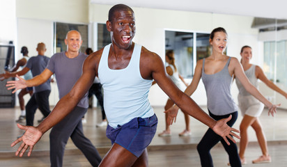 Cheerful people practicing vigorous lindy hop movements in dance class