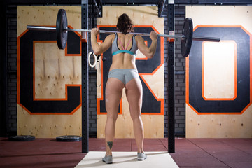 Sport and health theme. A beautiful sexy girl with a bare booty in a bikini stands tired near the bar and rests after a hard training session. Deadlift and training of leg and back muscles Wall mural