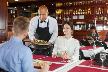Waiter serving young couple