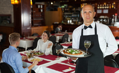 Waiter with serving tray meeting guests