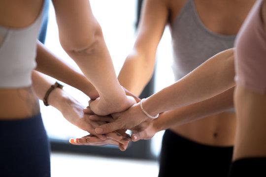 Sportive women stack hands showing team spirit at training