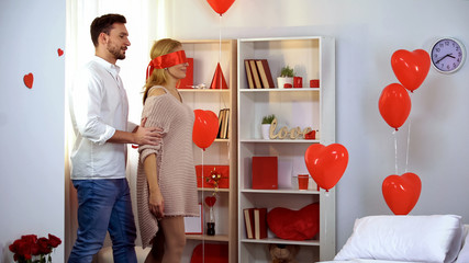 Man leading blindfolded with red ribbon lady into beautifully decorated room