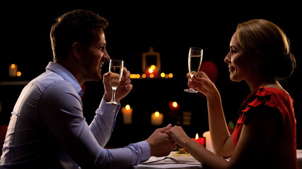 Man and lady holding hands and drinking champagne, romantic dinner in restaurant