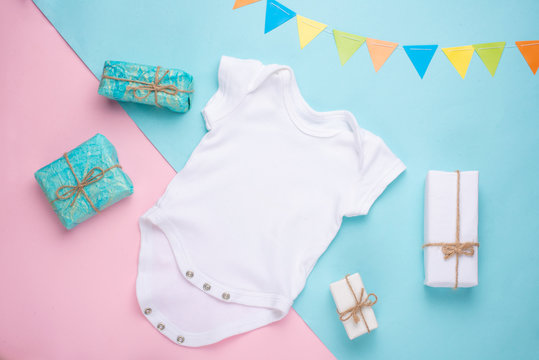 mockup Flat Lay white children shirt with gifts on a colored background. Layout for the design and placement of logos, advertising, children's party baby shower, children's birthday