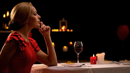 Pensive woman waiting for boyfriend late on romantic dinner in restaurant
