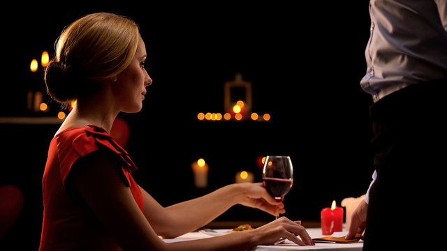 Waiter giving pretty lady bill, luxurious restaurant, consumer rights protection