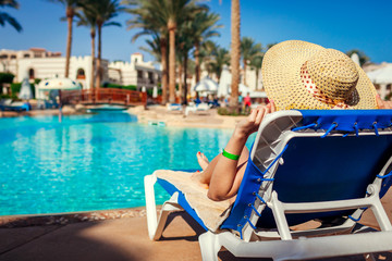 Woman relaxing by swimming pool lying on chaise-longue. Summer vacation. All inclusive