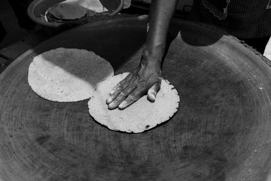 hand cooking tortillas on a comal