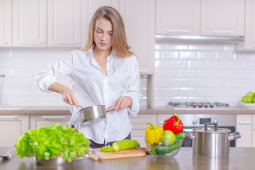 Happy young girl preparing healthy food in the kitchen