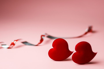 Two red velvet hearts in soft focus on a pink background. Background with copy space for Valentine's day or wedding