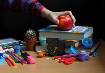 Front view of the table where school supplies, books, watches, cactus on a black background and a child's hand in a checkered shirt holds a red apple. Back to school. The concept of healthy food