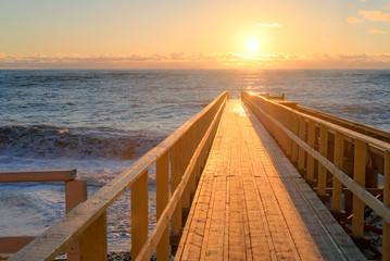 Yellow sun lights big storm waves. Sunset on the sea. Beautiful nature.